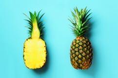 Cały ananas i połówka pokrajać owoc na błękitnym tle Odgórny widok kosmos kopii Jaskrawy ananasa wzór dla minimalnego obraz stock