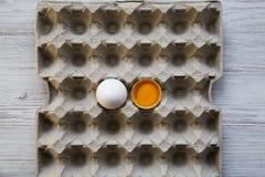 Cały i łamany jajko na tacy, odgórny widok biały tła drewniane Fotografia Stock