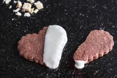 Cały serce kształtujący czekoladowy ciastko z złamane serce kształtującym brązu ciastkiem na czarnym marmuru kontuarze, zakończen obraz stock