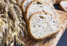 Całej banatki chleb z pszenicznymi ucho i ziarnami, chlebów plasterki na wo Fotografia Stock
