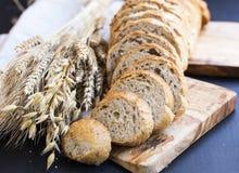 Całej banatki chleb z pszenicznymi ucho i ziarnami, chlebów plasterki na wo Zdjęcie Stock