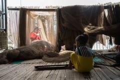 Ca Mau,越南- 2016年12月6日:与使用在她的母亲修补工作掩网附近的女儿的Fisher家庭在Ngoc Hien, Ca Mau二 图库摄影