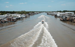 Ca Mau riverside residential with motor boat Stock Photos