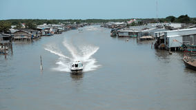 Ca Mau riverside residential with motor boat Stock Photography