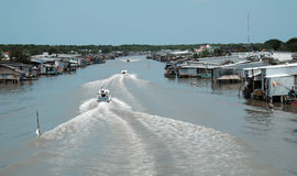 Ca Mau riverside residential with motor boat Stock Images
