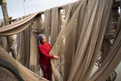 Ca Mau, Vietnam - Dec 6, 2016: Vietnamese woman mending casting net in Ngoc Hien, Ca Mau district, Vietnam.  Stock Images