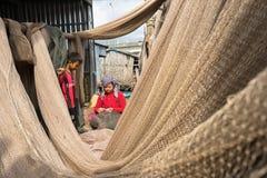 Ca Mau, Vietnam - Dec 6, 2016: Vietnamese woman mending casting net in Ngoc Hien, Ca Mau district, Vietnam.  Royalty Free Stock Photos