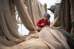 Ca Mau, Vietnam - Dec 6, 2016: Vietnamese woman mending casting net in Ngoc Hien, Ca Mau district, Vietnam.  Stock Photography