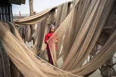 Ca Mau, Vietnam - Dec 6, 2016: Vietnamese woman mending casting net in Ngoc Hien, Ca Mau district, Vietnam.  Stock Photo