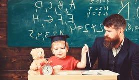 Ca?oe estudos felizes individualmente com pai, em casa Conceito de educa??o individual Professor e aluno no barrete fotografia de stock
