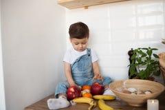 Ca?oe ter uma tabela completamente do alimento biol?gico Crian?a alegre que come a salada e frutos saud?veis Beb? que escolhe ent fotografia de stock