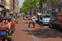 CA typical Amsterdam street with cyclists and cafes, Holland, Ne Royalty Free Stock Photography