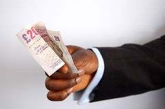 For the Cab!. This is an image of a black businessman offering 20 pound note royalty free stock images