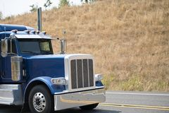 Cab of big rig blue bonnet semi truck driving on the road with h. Powerful professional big rig semi trucks tractors with large cabs and hood motors are used by stock images