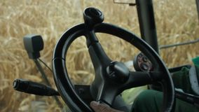 In the cab of combine harvester gathering corn Stock Photos