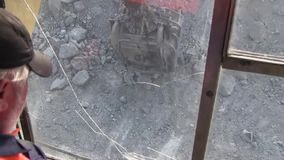 The cab of the excavator driver. The driver of the excavator looks at the slave bucket and stones through the glass stock video