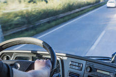 Cab of the truck while driving. The driver is holding the steering wheel and is driving a truck on the highway. Free place for your text is in the right side of Stock Photos