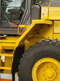 Yellow Wheel Loader. Cab of a yellow forklift truck with large rubber wheels Royalty Free Stock Photos
