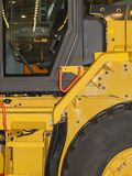 Yellow Wheel Loader. Cab of a yellow forklift truck with large rubber wheels Stock Images