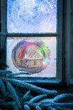 Cabaña adorable del pan de jengibre para la Navidad en ventana congelada Fotografía de archivo