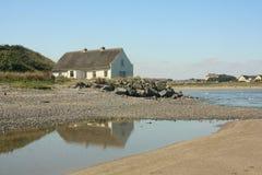 Cabaña cubierta con paja por el mar Foto de archivo libre de regalías