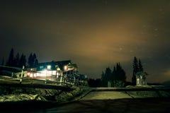 Cabaña de la montaña debajo del cielo nocturno Fotos de archivo libres de regalías