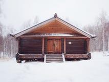 Cabaña de madera de madera en bosque del invierno Fotografía de archivo libre de regalías