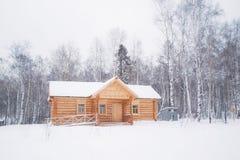 Cabaña de madera de madera en bosque del invierno Fotos de archivo libres de regalías
