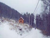 Cabaña de madera de madera en bosque del invierno y silueta de la mujer Imágenes de archivo libres de regalías