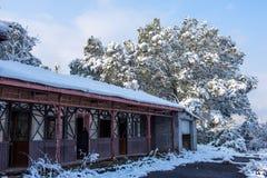 Cabaña de madera en bosque de la nieve del invierno Fotos de archivo