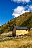Cabaña de madera en la base de montañas Foto de archivo