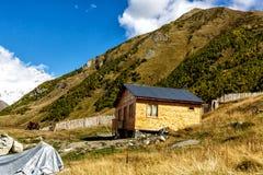 Cabaña de madera en la base de montañas Fotos de archivo libres de regalías