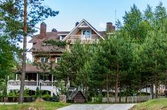 Cabaña de madera grande del tres-piso con el mirador en el estilo ruso clásico en el prado entre los árboles Foto de archivo