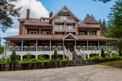 Cabaña de madera muy grande en el estilo rústico, tres pisos, ático y un pórtico, en la ubicación hermosa, rodeada por los árbole Foto de archivo libre de regalías