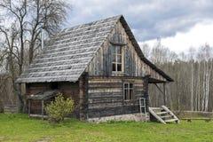 Cabaña de madera sola rodeada por paisaje rural Foto de archivo