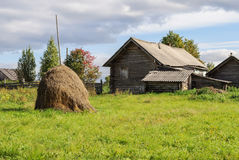 Cabaña de madera vieja con el pajar en el pueblo, día soleado del otoño Fotos de archivo