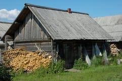 Cabaña de madera vieja con la pila de leña Fotos de archivo libres de regalías
