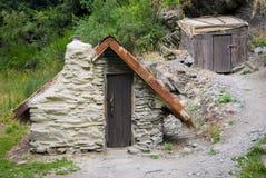 cabaña del Fango-ladrillo con el techo saltado al lado de la cabaña de madera del almacenamiento Fotografía de archivo libre de regalías