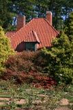 Cabaña del país en jardín formal Foto de archivo