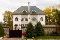 Cabaña detrás de las puertas del labrado-hierro en paisaje del otoño Fotos de archivo libres de regalías