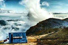 Cabaña en un pico con la visión en las nubes hermosas Fotos de archivo libres de regalías