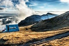 Cabaña hermosa en luz del sol en un pico Imagen de archivo libre de regalías