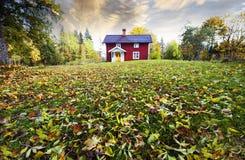 Cabaña, hojas de otoño y colores solos Imagen de archivo libre de regalías