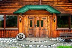 Cabaña marrón de madera en el campo con una rueda en el pórtico imagen de archivo