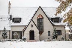 Cabaña pintada blanca encantadora del ladrillo con los acentos de cobre durante las nevadas con las hojas de otoño aún en árboles fotos de archivo