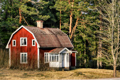 Cabaña roja vieja en un cerco rural Fotos de archivo libres de regalías