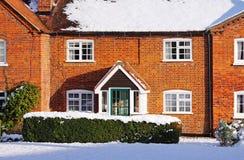 Cabaña rural inglesa del ladrillo rojo en la nieve Imagen de archivo