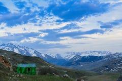 Cabaña verde en un paisaje de la montaña en la puesta del sol foto de archivo libre de regalías
