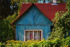Cabaña vieja del país del verano con el tejado rojo Imagenes de archivo
