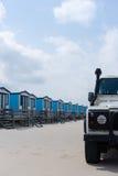 Cabañas azules para el alquiler en una playa arenosa con un 4x4 Imágenes de archivo libres de regalías